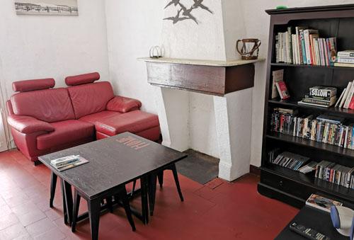 salon du gite avec ecran plat , livres, canapé